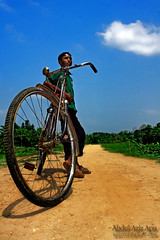 relaxation on wheels... ( (double-A Apu)) Tags: blue boy portrait man color bicycle clouds landscape wheels lifestyle usm relaxation bangladesh ef 1740mm f4l ef1740mmf4lusm 40d canon40d birishiri