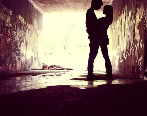 Fotografía de una parejita abrazada a contraluz en un túnel