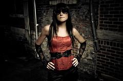 super heroine (Beyond Broken Media) Tags: red woman brick sunglasses leather female belt alley lace pipes longhair dramatic skirt pole gloves superhero corset epic rockandroll moviestill handsonhips strobist