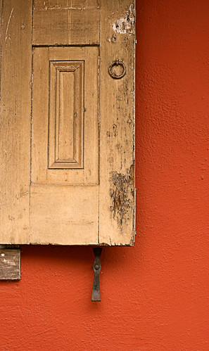 old shutter against orange wall