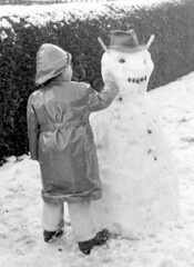 It just needs that finishing touch (theirhistory) Tags: winter boy snow hat garden kid sticks snowman child coat sneeuw ears rubber kind hedge jas mackintosh jongen hoed rainhat souwester sneeuwt rubbertrousers rubbercoat