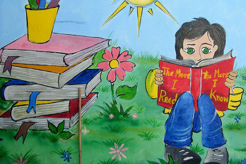 "graffiti of a small green-eyed child reading a book, with a stack of books next to her; the title of the book reads, ""the more I read/the more I know"""