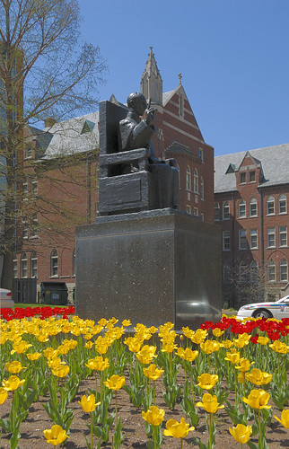 Statue of  the Venerable Pope Pius XII, at Saint Louis University, in Saint Louis, Missouri, USA - statue with tulips in bloom