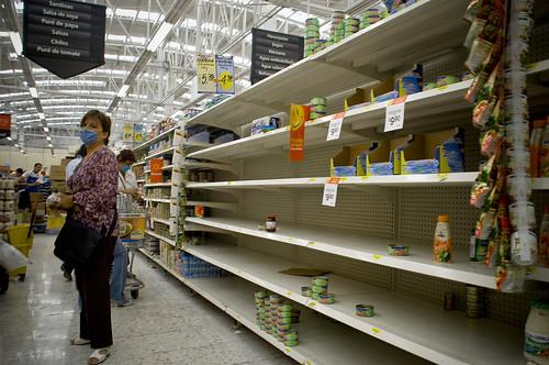 Mujer con mascarilla comprando en un supermercado con estanterías casi vacías