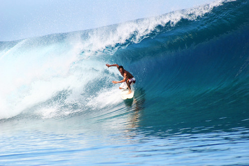 A surfer surfing the perfect wave at Teahupoo, Tahiti.