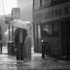 romance (memetic) Tags: street bw man bus wet water rain umbrella hongkong blackwhite candid delta stranger 400 faceless heavy ilford typhoon doubledecker p6 pentaconsix sheungwan