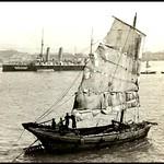 MODERN AND ANCIENT MODES OF PLYING THE SEAS -- A Chinese Junk and a British Battleship in OLD HONG KONG, CHINA thumbnail