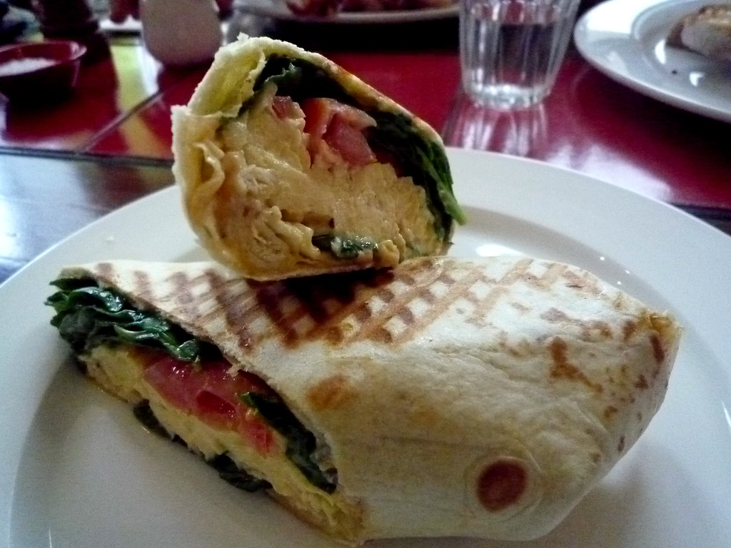 Burrito with scrambled egg, wilted spinach, tomato and chilli jam