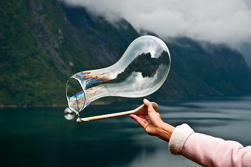 Creating soap bubbles over the fjord with a string and a spoon by Odinodin.com