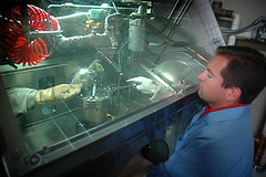 Nuclear technicians work through a glovebox on radioactive components at INL's Materials and Fuels Complex