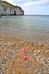 WLTM bucket (Charles Frost) Tags: sea sky cliff beach water clouds canon eos coast seaside sand stones yorkshire pebbles cave spade flamborough 40d