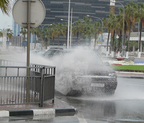 A car sprays water as it passes through a Doha puddle