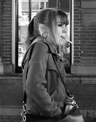 SMOKER AT THE STATION (Akbar Simonse) Tags: street people urban bw holland netherlands girl bag zwartwit cigarette candid streetphotography denhaag x earrings smoker thehague streetshot hollandspoor dedoka 200000000stagelovers akbarsimonse