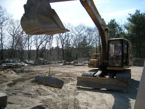 back hoe picking up granite step