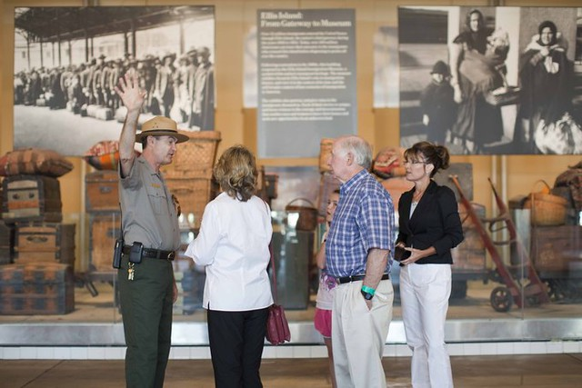 Sarah Palin stands with 3 family members inside the Ellis Island museum. A tour guide faces them and raises his hand, gesturing away from the back wall, which displays large photographs of immigrants from the early 20th century and many old valises and suitcases.