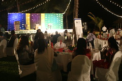 People sitting around dinner tables in front of a stage on the beach