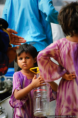 Curious! (Shabbir Siraj) Tags: morning pakistan streets cute girl kid bottle october purple little karachi ethnic 2008 sindh khi needy bahadurabad