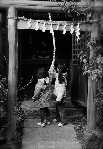 Children Ring A Bell At A Shinto Shrine