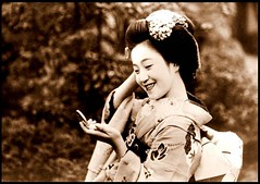 A PRETTY MAIKO TALKING ON A CELL PHONE HELD TO...