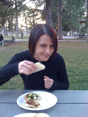Taco enthousiast Carmen enjoying a delicious Carne Asada taco as the sun sets.