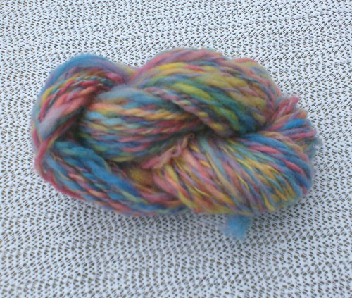 Skein of blue red yellow pink green purple handspun wool yarn