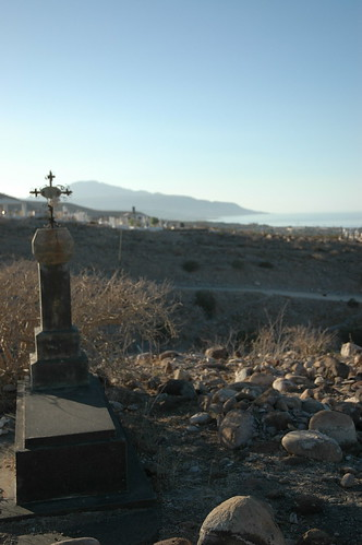 Metal cross, gravesite, boulders, view from the huge San Rosalita Cemetary, Baja California Sur, Mexico by Wonderlane
