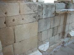 Podium de la escena del Teatro. Todavía se aprecian los agujeros que servían para colocar los anclajes de hierro, para la sujeción de las placas de mármol.