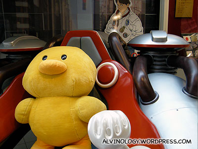 Nissin chick sitting in a model of the futuristic car seen in the hit manga, Akira