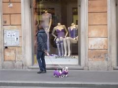 immagine di una donna che passa davanti alla vetrina di un negozio di abbigliamento