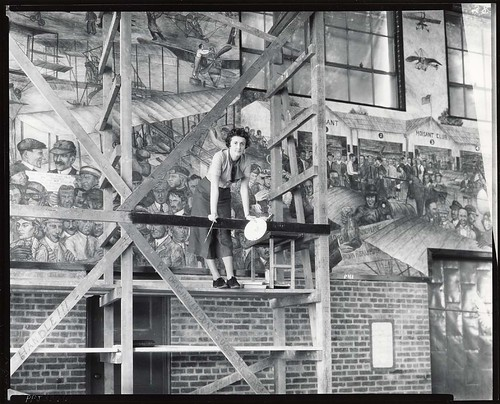 Aline H. Rhonie, American painter, 1909-1963, at work on aviation mural at Roosevelt Field, Garden City, New York