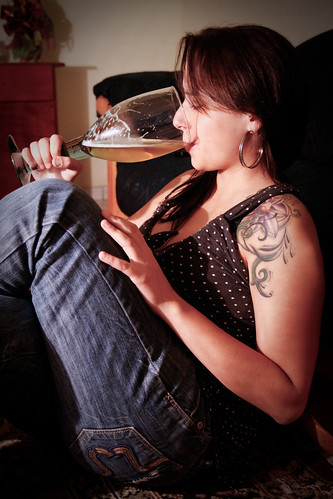 Girl drinks with tattoo arm