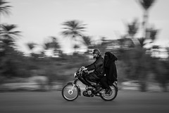 Life on the road - 5 (aminefassi) Tags: life road street portrait people blackandwhite bw motion black speed canon 50mm movement strada noir candid riding morocco motionblur maroc moto motorcycle marrakech marrakesh panning blanc sl1  byke palmeraie  ef50mmf18 mobylette  100d aminefassi vision:mountain=069 vision:sky=0502 vision:outdoor=09