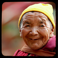 The Little Sunshine of Ladakh (designldg) Tags: red portrait people woman india smile yellow closeup colours friendship emotion bokeh expression buddhist religion happiness buddhism nun panasonic soul elder devotion tibetan himalaya spiritual shanti leh dignity freetibet contrejour dharamsala ladakh femininity  corporeal indiasong dmcfz18