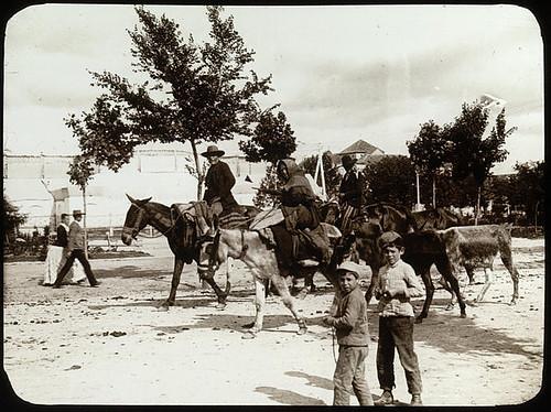 Lestrange. Place avec des hommes montés sur des chevaux ou des mulets, une femme sur un âne, deux enfants au premier plan, un couple passe à larrière-plan.