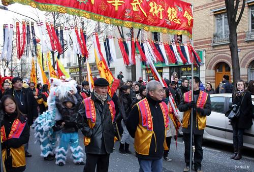 Chaque association en rapport avec la Chine défile, précédée de leur bannière respective