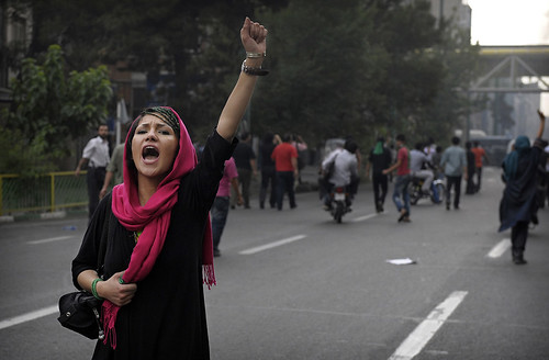 A young Iranian woman holds her fist high, shouting in a street.