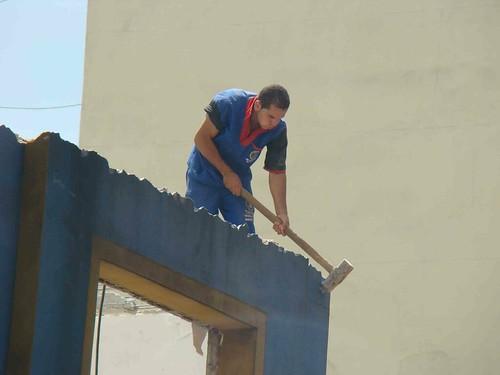 Sem equipamentos, trabalhador se equilibra no alto de imóvel em demolição