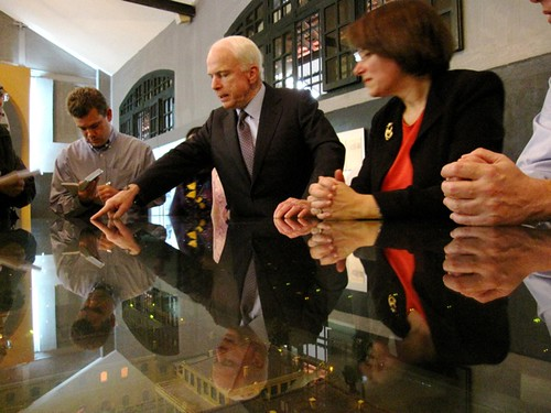 John McCain with Sen. Amy Klobuchar (right) points out the location of his cell at the Hoa Lo Prison Museum in Hanoi, April 8, 2009.