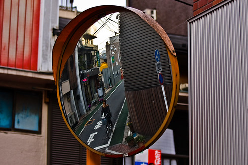 traffic crossing mirror with a man on a bike
