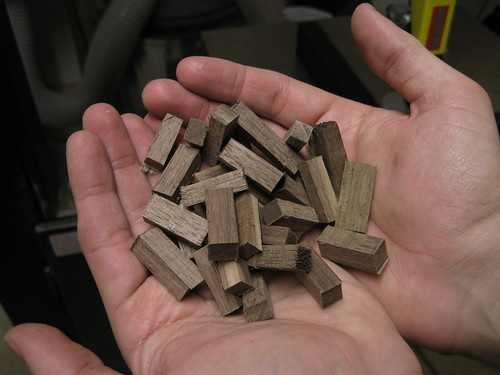 32 square walnut pegs cut out of a larger square rod on the band saw