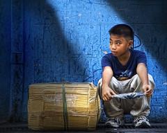 Manila, Philippines - It is a long wait (Mio Cade) Tags: street blue light boy shadow portrait color colour wall shirt photography kid waiting child box manila wait balance merchandise jeepney patience tansport