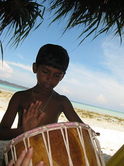 A local boy plays with Carrie's new drum that we were trying to ship back home (taken by Carrie)