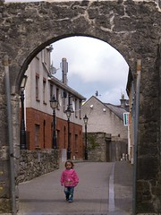 Alone Under the Arch (moorepat) Tags: kilkenny ireland portrait girl walking children alone candid olympus photograph lonely e3 relaxed youngchild creativecomments patmoorephotographerkilkenny