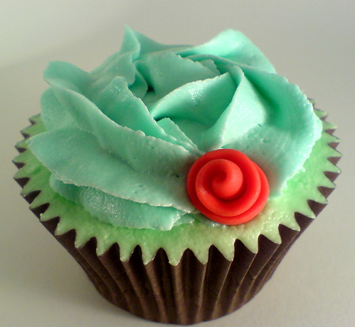 Eggless chocolate cupcake topped with red ribbon rose