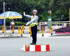 Chinese Policewoman directing traffic at junction