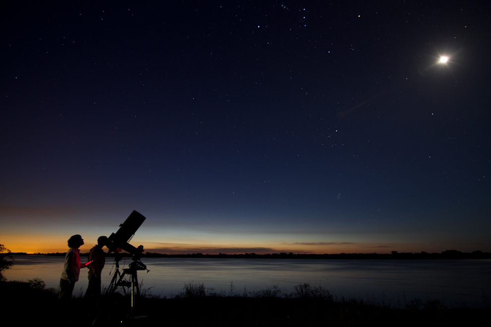 Rodrigo Ríos se apresta a calibrar y configurar su telescopio Celestron usando de referencia distintos cuerpos celestes, mientras cae la noche en Zanjita. (Tetsu Espósito - Zanjita, Paraguay)