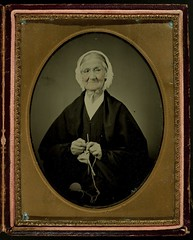 Oval framed portrait of older woman knitting
