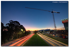Love And Hate In Canberra (Sam Ili) Tags: road light sunset sky sun building cars canon construction traffic trails australia symmetry canberra hdr photomatix 450d canberrasunset canon1022mm3545