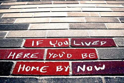Fotografía de una pintada en blanco sobre ladrillo rojo que reza If you lived here you'd be home by now