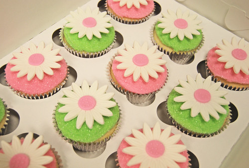 pink and green sparkle icing cupcakes topped with daisies for a baby shower